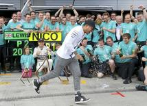 Mercedes Formula One drivers Lewis Hamilton of Britain (front) and Nico Rosberg of Germany celebrate their first and second places with the team after the Austrian F1 Grand Prix at the Red Bull Ring circuit in Spielberg, Austria, June 21, 2015.    REUTERS/Laszlo Balogh