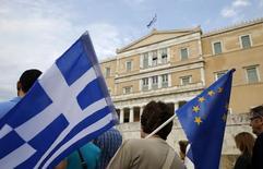 Manifestante segura bandeiras de Grécia e UE durante protesto em Atenas.  30/6/2015.  REUTERS/Yannis Behrakis