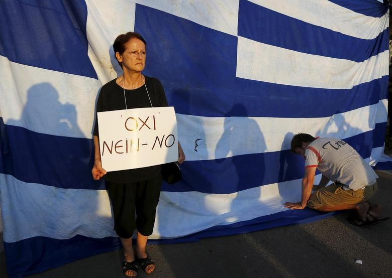 A protester holds a placard with the word ''No'' as another kneels to pay his respect in front of a Greek flag during an anti-austerity rally in Athens, Greece, June 29, 2015. REUTERS/Yannis Behrakis