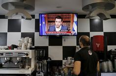 Официант в кафе смотрит телевизионное обращение премьер-министра Алексиса Ципраса в Афинах 1 июля 2015 года. REUTERS/Christian Hartmann