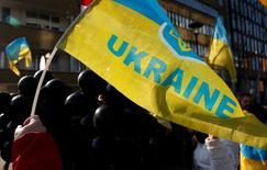 """Протестующие с флагами Украины в Брюсселе 12 февраля 2015 года. Министерство финансов Украины и ее кредиторы в среду сообщили о """"полезном обмене мнениями"""" и выработке условий соглашения о конфиденциальности, что позволит начать основные переговоры на следующей неделе. REUTERS/Francois Lenoir"""