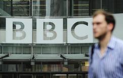 Un peatón camina junto al logo de la BBC, en el centro de Londres, 22 de octubre de 2012. La BBC dijo que recortará más de 1.000 empleos, debido a que espera recibir 150 millones de libras (234 millones de dólares) menos de lo previsto a partir de licencias en el próximo año fiscal porque los televidentes han dejado de ver programas por televisión y lo hacen por internet. REUTERS/Olivia Harris