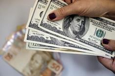 Mulher segura notas de dólares com notas de reais ao fundo. REUTERS/Sergio Moraes