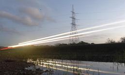 Unas torres de alta tensión junto a una autopista en Puchuncaví, Chile, sep 5 2014. La eléctrica chilena AES Gener contrató a un grupo de bancos para coordinar reuniones con inversionistas por una posible emisión de un bono en dólares bajo la regla 144a/Reg S, reportó el jueves IFR, un servicio informativo de Thomson Reuters.   REUTERS/Eliseo Fernandez