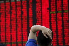 Las acciones chinas cayeron el viernes, después de que el regulador de valores del país dijo que abrió una investigación sobre una supuesta manipulación del mercado, en momentos en que Pekín lucha por evitar un derrumbe bursátil que podría dañar a una economía que ya se está desacelerando. En la imagen, una hombre mira un panel con precios en una oficina de Pekín, el 1 de julio de 2015. REUTERS/Kim Kyung-Hoon