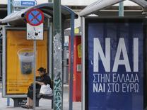 """Una nueva encuesta de opinión sobre el referéndum que Grecia realizará el domingo apunta a un resultado ajustado, con una intención de voto de un 44,8 por ciento para la opción del """"Sí"""", que favorece el rescate internacional a cambio de austeridad, y un 43,4 por ciento partidario del """"No"""" impulsado por el Gobierno heleno.  En la imagen se ve un cartel que dice """"Sí, a Grecia, Sí al euro"""" en una parada de autobús en Atenas el 2 de julio de 2015. REUTERS/Christian Hartmann"""