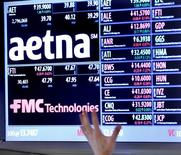 Un operador apunta hacia un tablero que muestra la información de Aetna, en la Bolsa de Nueva York, 20 de agosto de 2012. La aseguradora de salud Aetna Inc dijo que comprará a su rival menor Humana Inc por unos 37.000 millones de dólares en efectivo y acciones, en el mayor acuerdo a la fecha de la industria de seguros. REUTERS/Brendan McDermid