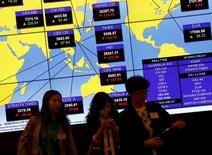 Tableau d'indicateurs des marchés asiatiques en temps réel, à Hong Kong. Les 21 plus importantes sociétés de courtage chinoises ont annoncé samedi qu'elles allaient collectivement investir au moins 120 milliards de yuans (17,4 milliards d'euros) pour tenter de stabiliser les marchés boursiers du pays, qui ont perdu près de 30% de leur valeur depuis la mi-juin. /Phoot prise le 29 juin 2015/REUTERS/Bobby Yip