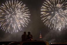 People watch the Macy's 4th of July Fireworks for Independence Day eplode over the East River from the rooftop of their car from the Pulaski Bridge in New York July 4, 2015. REUTERS/Andrew Kelly