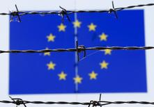 A barbed wire is seen in front of a European Union flag at an immigration reception centre in Bicske, Hungary June 25, 2015. REUTERS/Laszlo Balogh