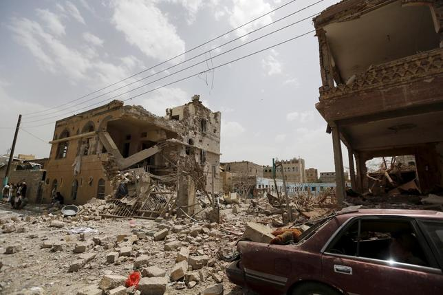 People sit near houses destroyed by a Saudi-led air strike in Yemen's capital Sanaa July 3, 2015. REUTERS/Khaled Abdullah