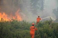 Firefighters tackle a wildfire near the town of La Ronge, Saskatchewan July 5, 2015 in a picture provided by the Saskatchewan Ministry of Government Relations. REUTERS/Saskatchewan Ministry of Government Relations/Handout via Reuters