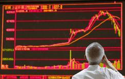 Un hombre mira un tablero electrónico que muestra la gráficas de los precios de las acciones en una agencia de la bolsa en Beijing, China, 6 de julio de 2015. Las acciones chinas cayeron el martes a pesar de una serie de medidas de apoyo anunciadas por Pekín en los últimos días, y luego de que el primer ministro chino, Li Keqiang, no mencionó el caos en el mercado en un comunicado sobre la economía. REUTERS/Kim Kyung-Hoon