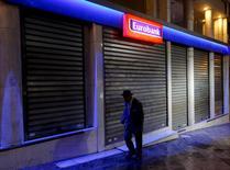 Un hombre camina junto a un banco en Atenas, Grecia, 28 de junio de 2015. Grecia emitirá el miércoles un decreto ministerial para extender un feriado bancario que ya se prolonga por ocho días laborales, dijo una fuente del gobierno, mientras Atenas intenta convencer a sus escépticos socios de alcanzar un nuevo acuerdo de ayuda. REUTERS/Yannis Behrakis