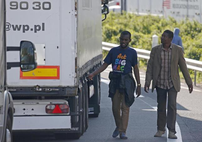 Migrants check the trailer of a truck during an attempt to make a clandestine crossing to England through the Channel tunnel as lorries wait on a road which leads to the Channel Tunnel terminal in Coquelles near Calais, northern France, July 1, 2015.  REUTERS/Vincent Kessler