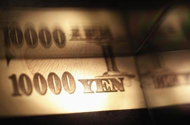 Light is cast on a Japanese 10,000 yen note as it's reflected in a plastic...
