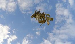 Долларовые купюры в небе над Севильей 16 ноября 2014 года. Чистый отток частного капитала из РФ во втором квартале 2015 года составил $20 миллиардов, следует из оценки Банка России. REUTERS/Marcelo Del Pozo
