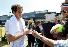 Andy Murray of Britain signs his autograph for fans after a practice session at the Wimbledon Tennis Championships in London, July 9, 2015. REUTERS/Suzanne Plunkett