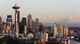 The Space Needle and Mount Rainier are pictured at dusk in Seattle, Washington March 12, 2014.    REUTERS/Jason Redmond