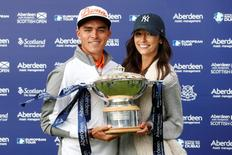 USA's Rickie Fowler celebrates his win with the trophy and his girlfriend Alexis Randock. Action Images via Reuters / Lee Smith