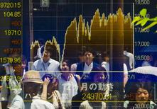 People are reflected in a board displaying market indices in Tokyo July 10, 2015. REUTERS/Thomas Peter