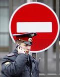 Полицейский говорит по телефону у японского посольства в Москве. 2 ноября 2010 года. Российский президент Владимир Путин подписал указ о сокращении максимальной штатной численности министерства внутренних дел на 110.000, или примерно на 10 процентов, согласно документу, размещенному на правительственном сайте в понедельник. REUTERS/Sergei Karpukhin