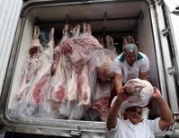 Unos trabajadores descargan carne de un camión en Sao Paulo, mayo 27 2015. JBS SA, la mayor distribuidora de carne del mundo, dijo el lunes que obtuvo un préstamo de hasta 1.200 millones de dólares para pagar por la adquisición de los activos de carne de cerdo de Cargill en Estados Unidos.  REUTERS/Paulo Whitaker