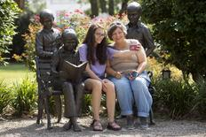 "Amy Burchfield and her daughter Scout Burchfield take a photo with the ""A Celebration of Reading"" sculpture at the Old Monroe County Courthouse, the setting of ""To Kill a Mockingbird""  in Monroeville, Alabama July 14, 2015. REUTERS/Michael Spooneybarger"