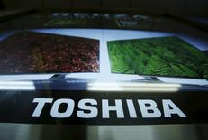 A logo of Toshiba Corp is seen next to an advertisement board for its Regza television in Tokyo, Japan, June 25, 2015. REUTERS/Yuya Shino