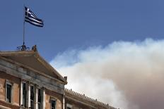 A Greek national flag flutters atop the parliament building as smoke from a raging wildfire rises in Athens July 17, 2015.  REUTERS/Alkis Konstantinidis