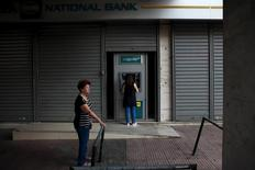 Women withdraw money from an ATM outside a National Bank branch in Athens, Greece, July 19, 2015.  REUTERS/Yiannis Kourtoglou