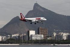 Un avión de la aerolínea TAM se prepara para aterrizar en el aeropuerto Santos Dumont, mientras se ve la estatua del Cristo Redentor en el fondo, en Río de Janeiro, Brasil, 1 de julio de 2015. La aerolínea brasileña TAM, unidad de Latam Airlines Group SA, anunció el lunes que decidió reducir gradualmente sus operaciones domésticas en entre 8 y 10 por ciento debido a un escenario económico complejo. REUTERS/Sergio Moraes