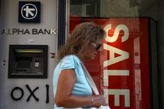 Mulher passa em frente a banco e loja anunciando promoção em Atenas.  21/7/2015.  REUTERS/Yiannis Kourtoglou