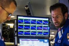 Трейдеры на торгах Нью-Йоркской фондовой биржи 29 июня 2015 года. Американские фондовые индексы снизились во вторник, так как результаты IBM и United Technologies разочаровали инвесторов.  REUTERS/Lucas Jackson