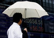 Un hombre mira un tablero que muestra el índice Nikkei en Tokio, 17 de julio de 2015. El índice Nikkei de la bolsa de Tokio cortó el miércoles una racha de seis días de ganancias, presionado por una caída en Wall Street, y las acciones relacionadas con Apple cayeron luego de que las previsiones de ingresos del gigante tecnológico incumplieron las expectativas del mercado. REUTERS/Thomas Peter