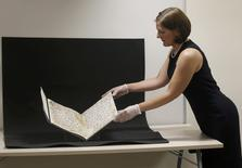 Conservator, Marie Sviergula holds a fragment of a Koran manuscript in the library at the University of Birmingham in Britain July 22, 2015. A British university said on Wednesday that fragments of a Koran manuscript found in its library were from one of the oldest surviving copies of the Islamic text in the world, possibly written by someone who might have known Prophet Mohammad. REUTERS/Peter Nicholls