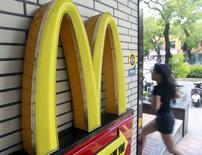 Una mujer corre junto a un local de McDonald's en Taipéi, Taiwán, 25 de junio de 2015. Las ganancias trimestrales de McDonald's Corp cayeron un 13 por ciento, afectadas por un declive global en sus ventas comparables debido a que menos clientes ingresaron a sus restaurantes. REUTERS/Pichi Chuang -