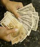 Pessoa troca reais por dólares em casa de câmbio no Rio de Janeiro. 07/05/2004 REUTERS/Bruno Domingos