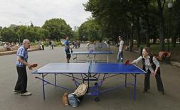 Люди играют в настольный теннис в Парке Горького в Москве 15 августа 2013 года. Выходные в Москве будут солнечными и теплыми, свидетельствует усредненный прогноз, составленный на основании данных Гидрометцентра России, сайтов intellicast.com и gismeteo.ru. REUTERS/Phil Noble