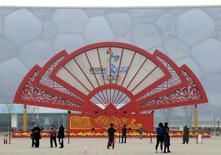 People walk past a installation in the shape of a fan bearing the bidding logo of Beijing 2022 Winter Olympics, in front of the National Aquatics Center, also known as the Water Cube, in Beijing, China, February 15, 2015. REUTERS/Stringer