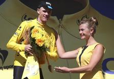 Team Sky rider Chris Froome of Britain wears the race leader's yellow jersey on the podium after the 110.5-km (68.6 miles) 20th stage of the 102nd Tour de France cycling race from Modane to Alpe d'Huez in the French Alps mountains, France, July 25, 2015. REUTERS/Stefano Rellandini