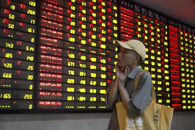 An investor looks at an electronic board showing stock information at a brokerage house in Nanjing, Jiangsu province, China, July 24, 2015. REUTERS/China Daily