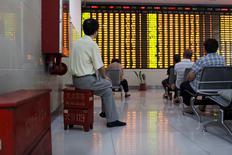 Un inversor se sienta en una caja que contiene un extinguidor mientras mira un tablero electrónico que muestra la información de las acciones en una correduría en Shanghái, China, 14 de julio de 2015. Las bolsas de Asia comenzaban la semana a la baja luego de unas pérdidas en Wall Street y ante las preocupaciones sobre China, mientras los inversores se preparan para una reunión de la Reserva Federal que podrían dar otro pequeño paso hacia el alza de las tasas de interés en Estados Unidos. REUTERS/Aly Song