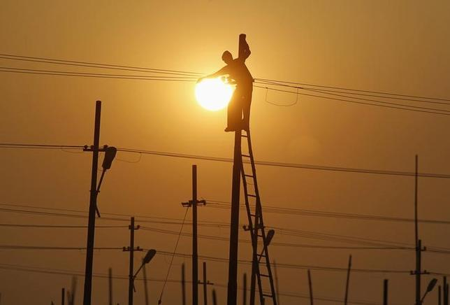 A worker is silhouetted against the setting sun while installing an overhead electric cable pole on the banks of river Ganges in Allahabad December 26, 2014. REUTERS/Jitendra Prakash/Files