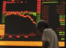 An investor stands in front of an electronic board showing stock information at a brokerage house in Fuyang, Anhui province, July 27, 2015.  REUTERS/Stringer