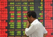 Un inversor frente a un tablero electrónico que muestra la información de las acciones, en una correduría en Fuyang, China, 28 de julio de 2015. Las acciones chinas cayeron el martes en una sesión volátil, aún después de que Pekín se comprometió a ofrecer más apoyo después de los valores se hundieron un 8 por ciento en la sesión anterior, aumentando las preocupaciones sobre la estabilidad financiera en la segunda mayor economía del mundo. REUTERS/Stringer