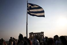 A Greek flag flutters in the wind above tourists visiting the archaeological site of the Acropolis hill in Athens, Greece July 26, 2015.  REUTERS/Ronen Zvulun