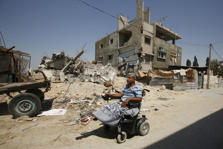 Palestinian maths teacher Ali Wahdan moves his motorised wheelchair past the ruins of his house, that witnesses said was destroyed by Israeli shelling during a 50-day war last summer, in Beit Hanoun town, in the northern Gaza Strip July 6, 2015.  REUTERS/Suhaib Salem