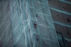 Imagen de archivo de un trabajador en una construcción observando una protesta en las calles de Santiago, jun 10 2015. El desempleo de Chile habría subido levemente a un 6,7 por ciento en el trimestre móvil a junio, en una señal del creciente impacto de la debilidad de la economía en el mercado laboral, reveló el miércoles un sondeo de Reuters.  REUTERS/Ricardo Moraes