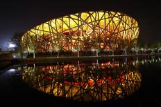 "The National Stadium, also known as the ""Bird's Nest"", is seen reflected in a lake before Earth Hour at the Olympic Park in Beijing, March 29, 2014. REUTERS/Kim Kyung-Hoon"